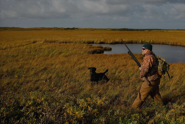 men hunter in camo clothes looking for a hunt