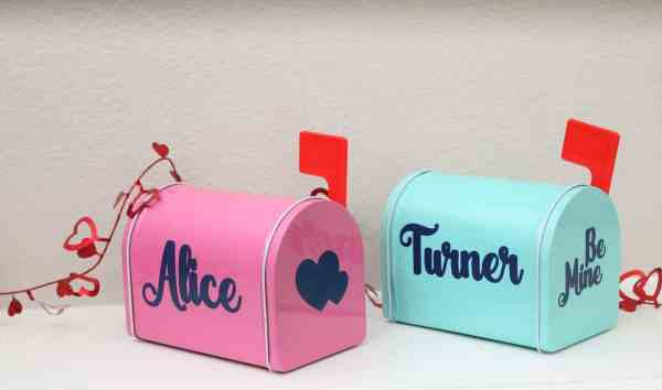 pink metal mail box with red flag that has the name Alice and hearts on it, and a light blue mail box with red flag with the name Turner on it and the words be mine