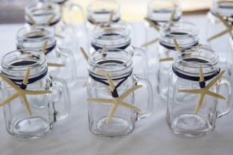 Starfish were tied onto mason jars with navy raffia. Mason jars by SKO Designs. Photography by Organic Photography.