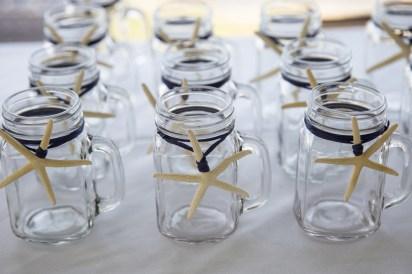 Starfish were tied onto mason jars with navy raffia. Mason jars by SKO Designs. Photography by Organic Photography.