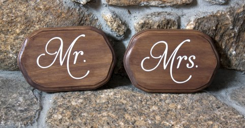 Stained wood Mr. & Mrs. chair signs with white glossy vinyl lettering.