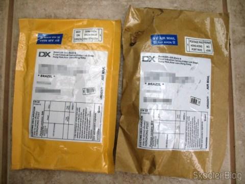 Os dois pacotes não tributados da DealExtreme: à esquerda no envelope amarelo o CD do dongle Wi-Fi e à direita no pacote pardo os cinco porquinhos