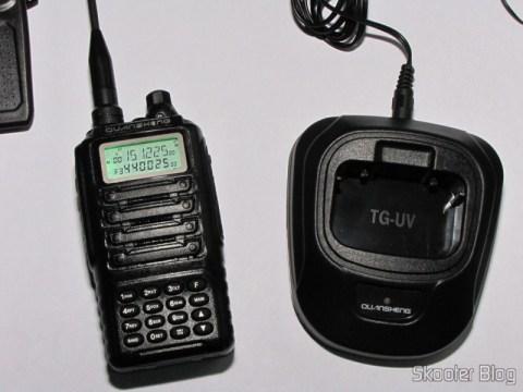 O Rádio HT Quansheng Walkie-Talkie Multi-Banda VHF/UHF, Dual Frequency, com VOX, Lanterna e Rádio FM ao lado do carregador
