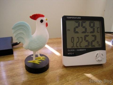 Relógio-Termômetro-Higrômetro Digital ao lado do clássico Galo do Tempo, popular instrumento de medida de umidade nos anos 80