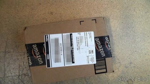 Pacote da Amazon coma a Câmera Digital Canon PowerShot ELPH 330 HS 12.1 MP Wi-Fi CMOS Zoom Óptico 10X Lentes 24mm Video Full HD 1080p com cartão de memória 32GB, bolsa e bateria extra, em foto tirada pela Shipito