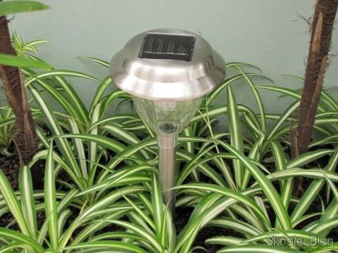 Lâmpada de Jardim de Aço Inoxidável com Luz de LED Branca Auto-Recarregável com Energia Solar (1*AA) (Stainless Steel Solar Powered Self-Recharged LED White Light Lawn Lamp (1*AA)) instalada, carregando durante o dia.