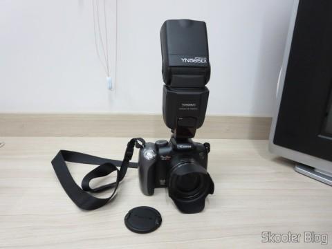 A Canon PowerShot SX10 IS que costuma fazer as fotos que você vê aqui no Skooter Blog, com o flash Flash TTL YongNuo Speedlite YN565EX c/ LCD 2.0″ para Canon DSLR (YongNuo Y565EX 2.0″ LCD TTL Flash Speedlite Speedlight for Canon DSLR – Black (4 x AA)), que você já viu aqui no Skooter Blog, acoplado.