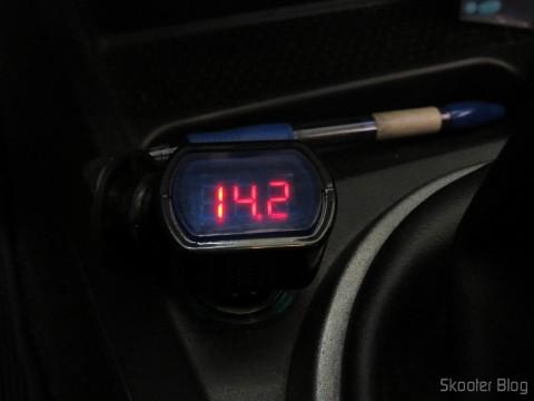 Medidor de Tensão de Bateria Automotiva com display LED e Conector para Tomada de Acendedor de Cigarros, em funcionamento, com o motor do carro ligado