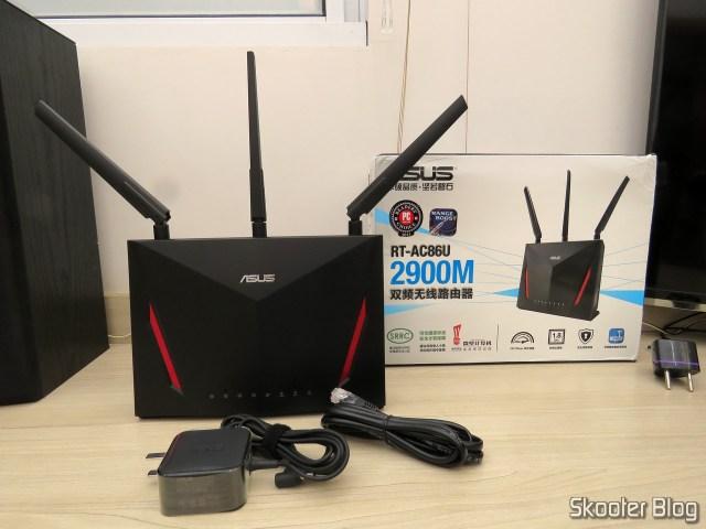 Roteador ASUS RT-AC86U, fonte de alimentação e cabo Ethernet.
