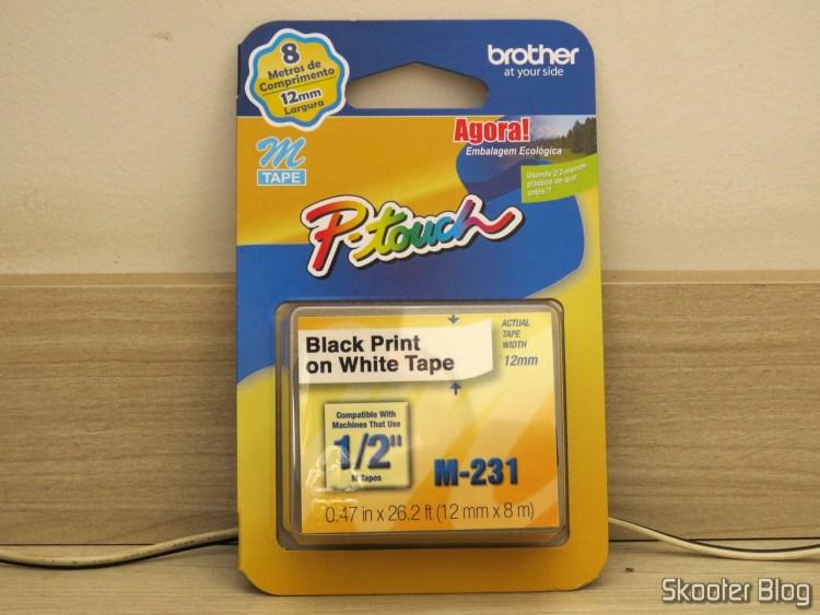 Fita p/ Rotulador 12mm x 8m M-231 Brother - Impressão Preta em Fita Branca, em sua embalagem.