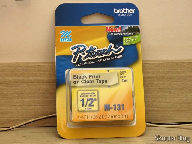 Fita p/ Rotulador M131 12mm Preto sobre Transparente Brother (Ref. M131), em sua embalagem.
