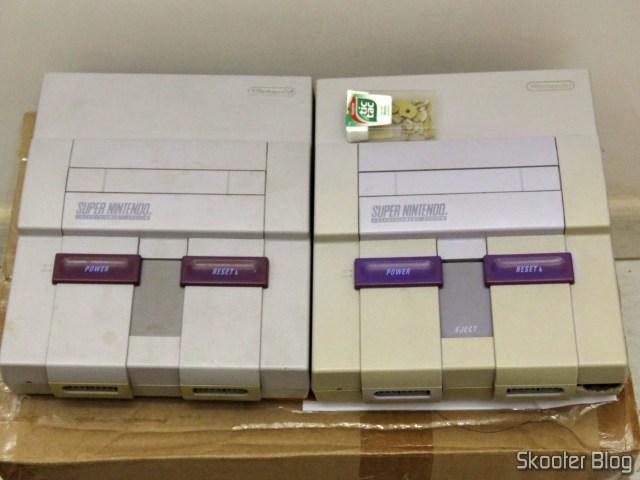 Os dois Super Nintendo, já montados com as partes corretas, e todas as pequenas partes quebradas no potinho.