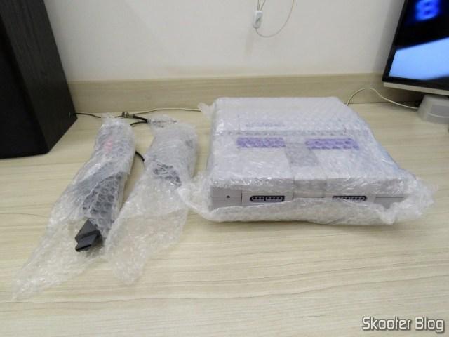 O console e os cabos A/V e R.F. embrulhados em plástico bolha.
