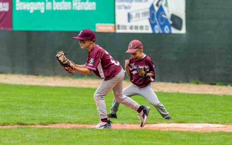 Pitcher und Baseman in Aktion versuchen einen Baseball zu fangen