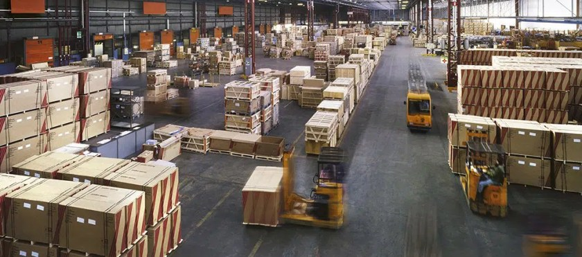 warehouse organization shown through forklifts driving through a busy warehouse
