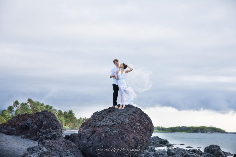 newlyweds stand on kona lava rock