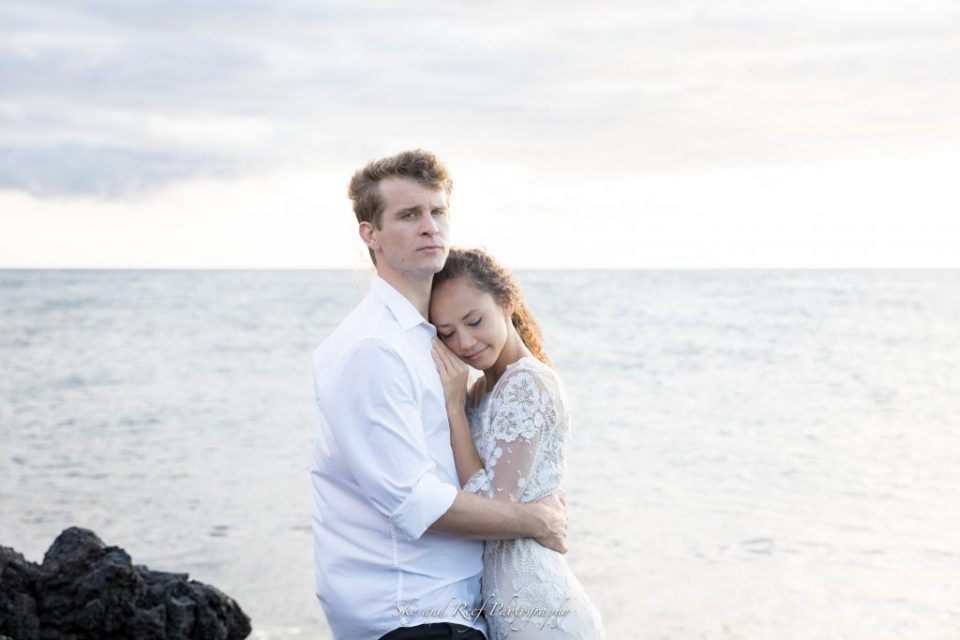 bride and groom hold each other on beach