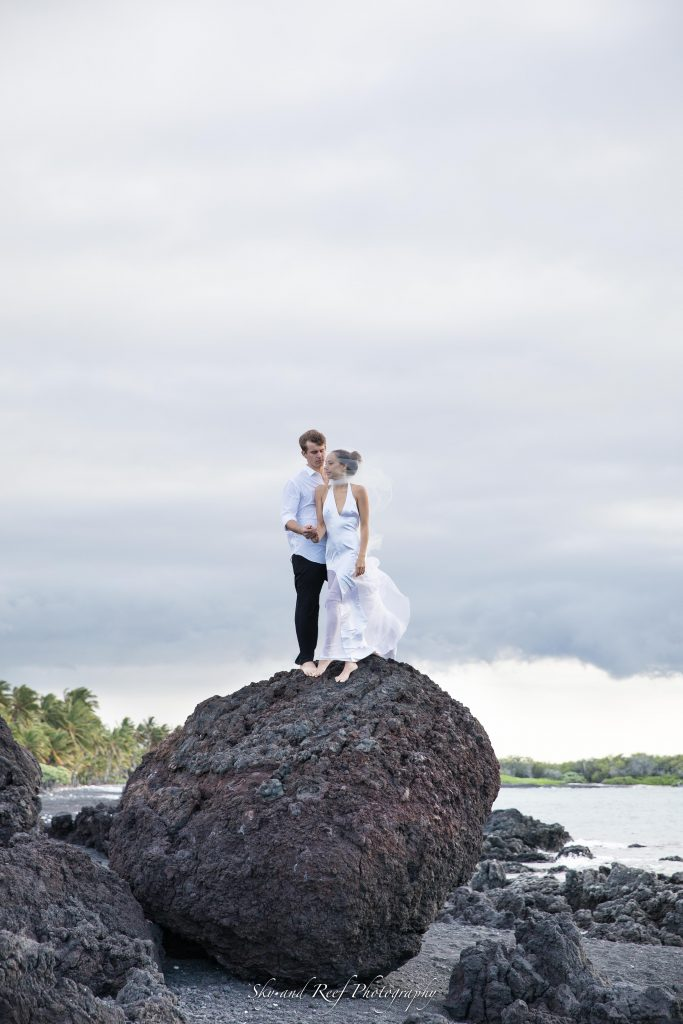 bride and groom stand atop a large rock on beach elopement