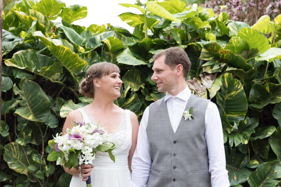 bride and groom in front of tropical plant at Kealakekua Bay Wedding Venue