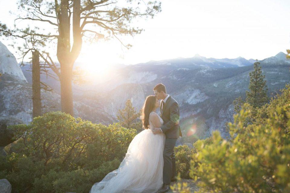 groom kisses bride on forehead in yosemite