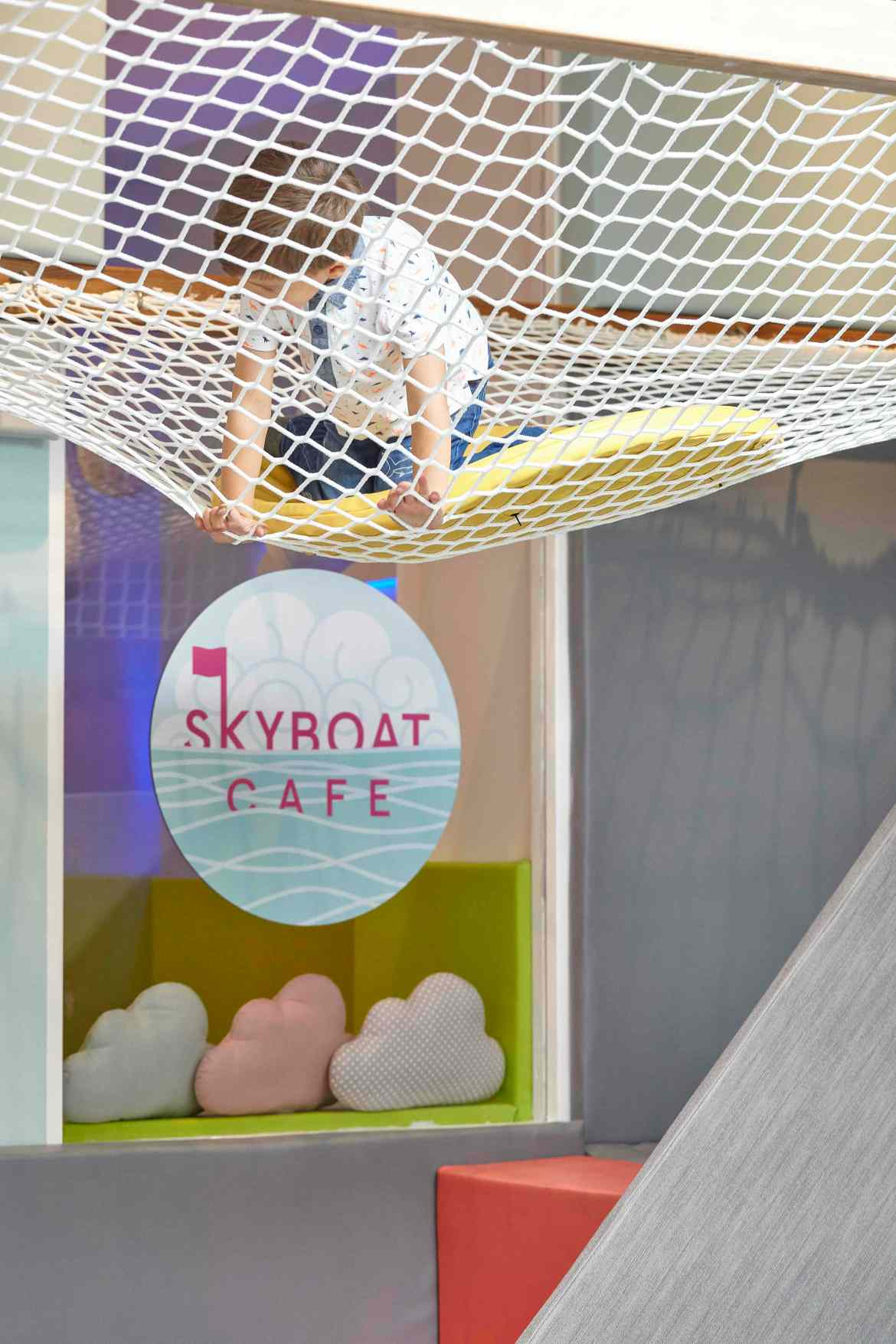 Young child climbing on netting in the soft play space