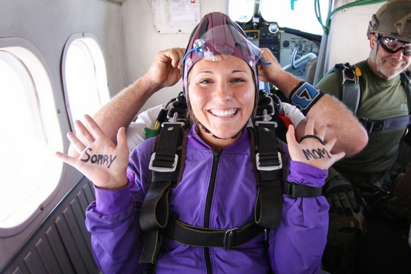tandem student writes on hands for skydiving video