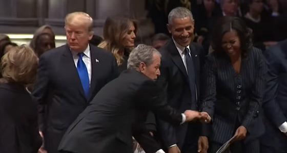 بالفيديو.. تكرار موقف غريب من بوش الابن مع زوجة أوباما بجنازة والده