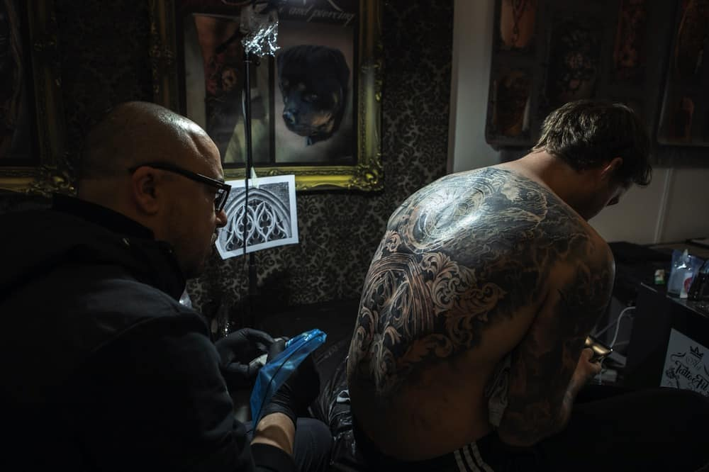man gets inked in a tattoo parlour