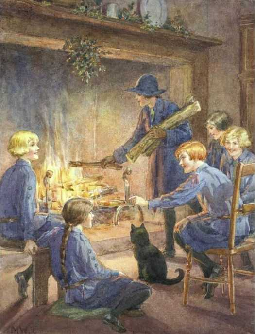 Girl guides sit around a fire. One girl puts logs on the fire. A black cat sits nearest.