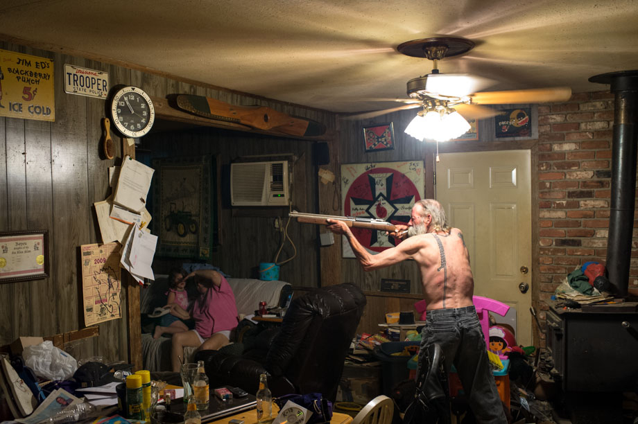 Carl, an Imperial Wizard of a southern-based Ku Klux Klan realm, takes aim with a pellet gun at a large cockroach (on the piece of paper just below the clock) while his wife and goddaughter try to avoid getting struck by a possible ricochet.