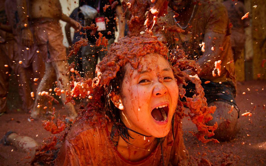Chaque année, des fêtard·es se jettent des tomates à la figureà l'occasion du festival de la Tomatina, dans la ville espagnole de Bunol, comme ici le 28 août 2019. Cette fête emblématique, qui célèbre le saint patron du village, est l'une des plus grandes batailles alimentaires du monde et attire chaque année nombre detouristes étrangèr·es.