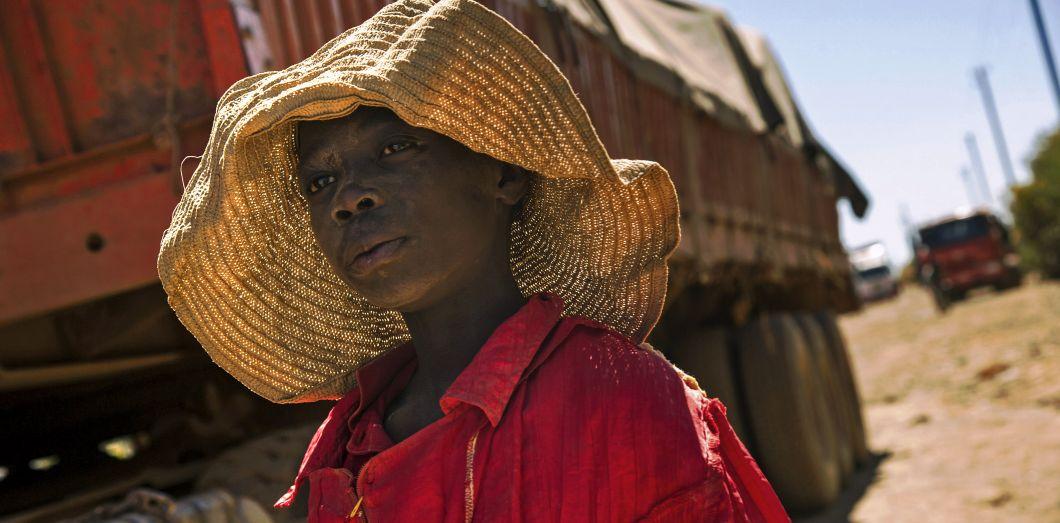 Un enfant passe devant un camion transportant des roches extraites d'une mine de cobaltà Lubumbashi, en République démocratique du Congo, le 23 mai 2016. Ces enfants seraient payés environ2 dollarspar jour.| Junio Kannah / AFP