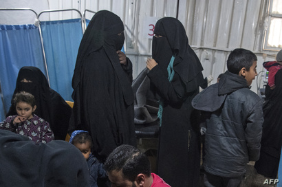 FILE - Two women, center, reportedly wives of Islamic State (IS) group fighters, wait with other women and children at a camp of al-Hol in al-Hasakeh governorate in northeastern Syria, Feb. 7, 2019.