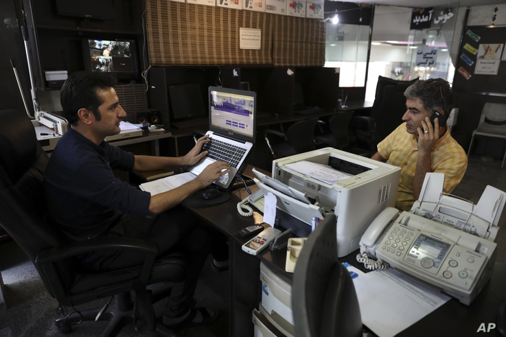 FILE - An internet cafe manager works on his computer as a man talks on his cell phone, in Tehran, Iran, July 25, 2019.