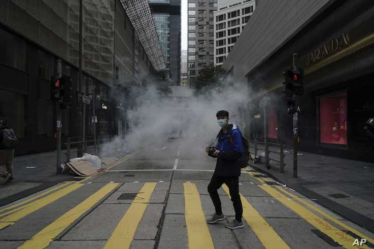 A man walks past as police use tear gas on protesters calling for electoral reforms and a boycott of the Chinese Communist…