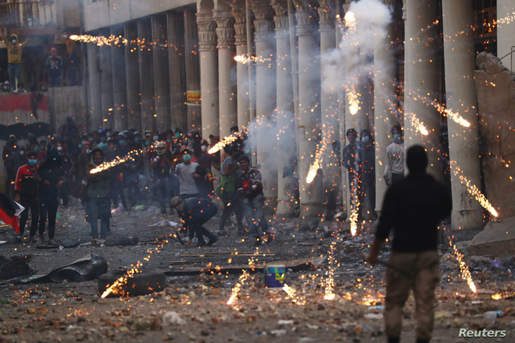 Iraqi demonstrators throw fireworks towards Iraqi security forces during the ongoing anti-government protests in Baghdad, Iraq…