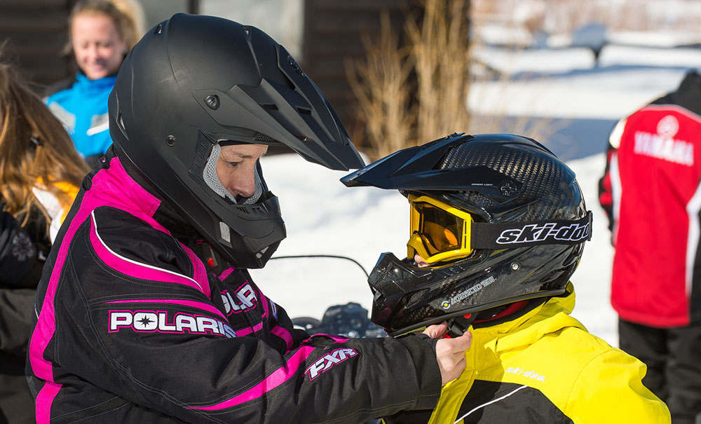 Helping child with helmet before riding