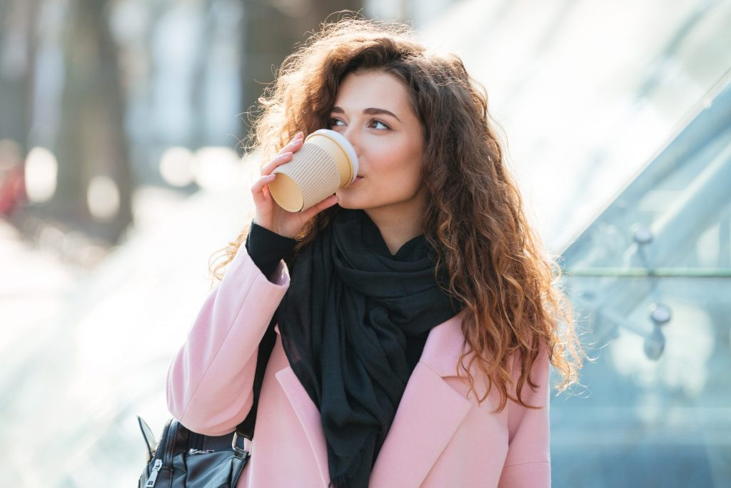 Cute young woman wearing pink coat drinking take away coffee in paper cup.
