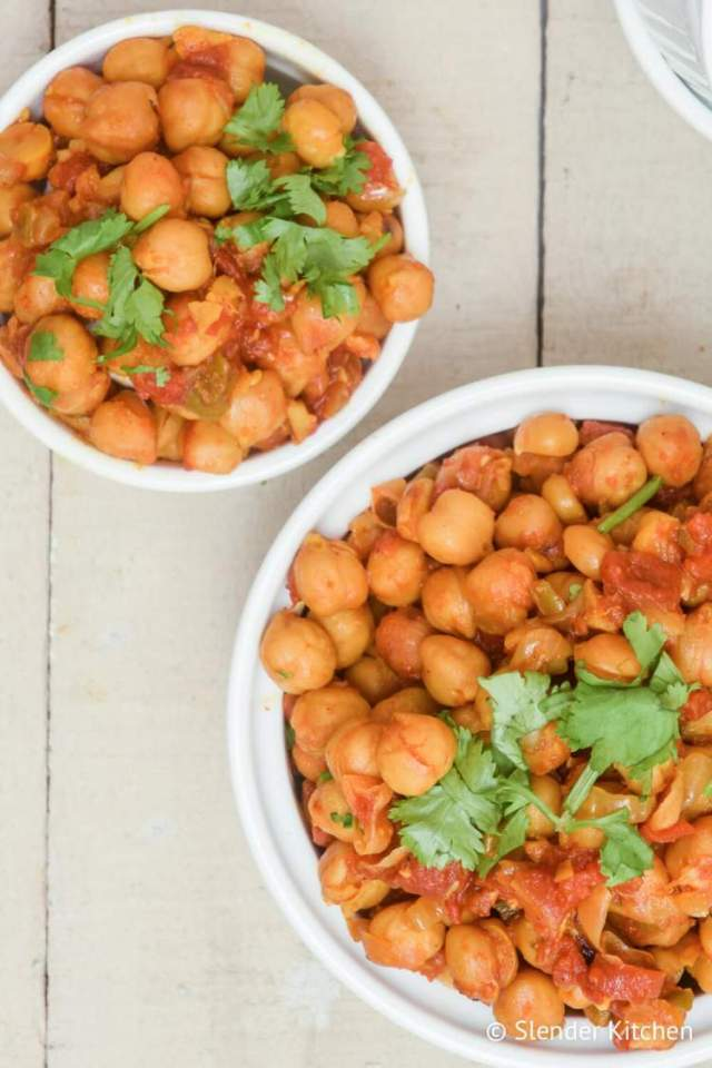 Chana masala with chickpeas cooked in curry tomato sauce in two white bowls.