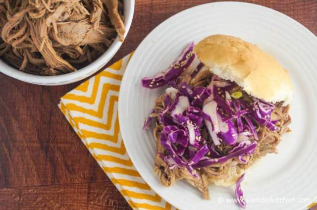 Crockpot Korean pork served in a sandwich roll with red cabbage.