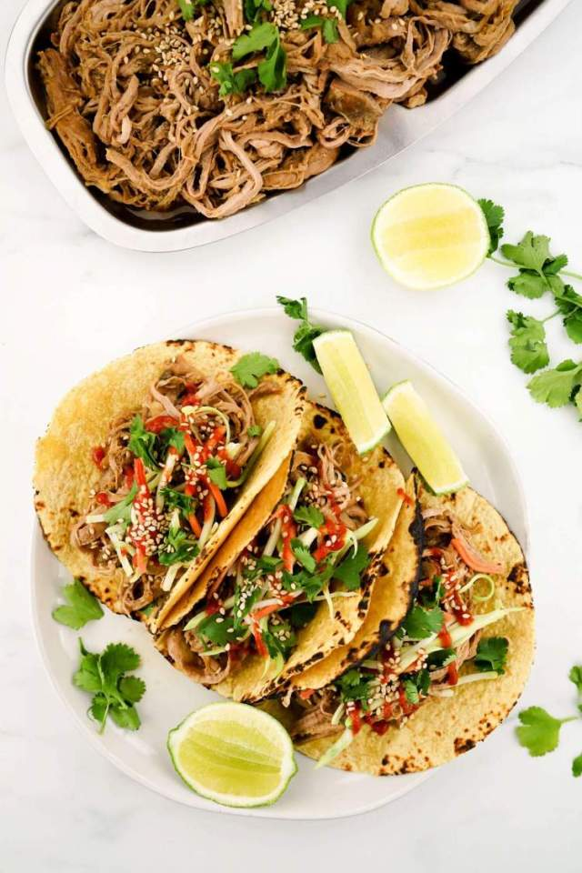 Slow Cooker Korean Pork on tortillas with slaw and Sriracha next to a plate of shredded pork.