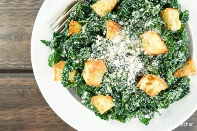 Healthy Kale Caesar with croutons and parmesan cheese on a plate on a wooden table.