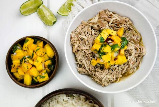 Healthy crockpot Jerk chicken in a bowl with brown rice, limes, and mango coleslaw.