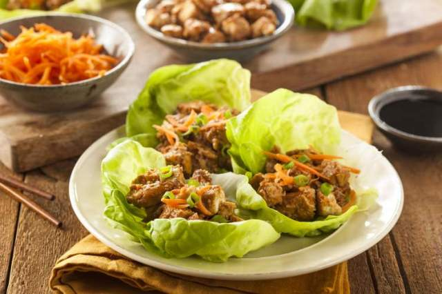 Slow Cooker healthy Korean chicken in lettuce wraps with carrots.