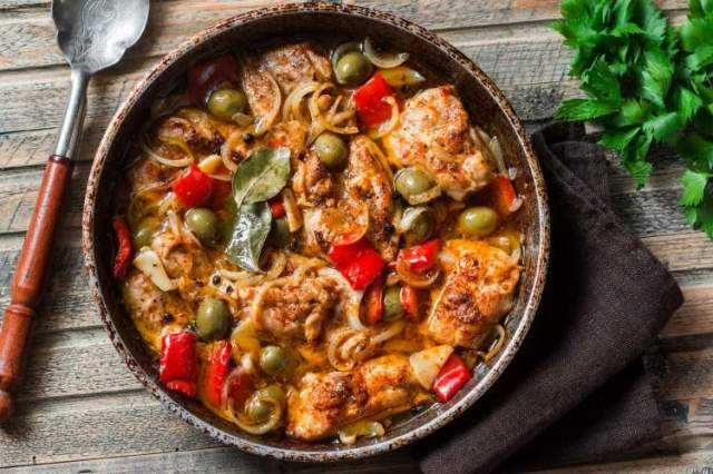Slow Cooker Chicken with tomatoes, olives, capers, and parsley in a skillet.