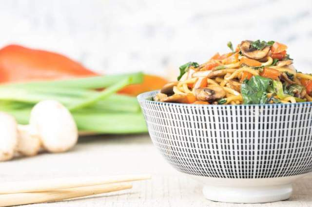 Spinach and mushroom lo mein with chopsticks in a bowl.