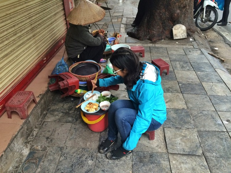 eating on tiny stools in the sidewalk. the vendors carry their entire restaurant on their backs