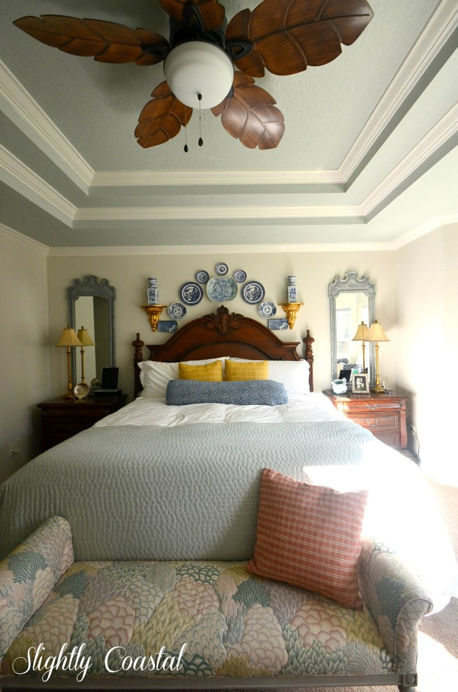 Master bedroom with matching mirrors and blue and white plates