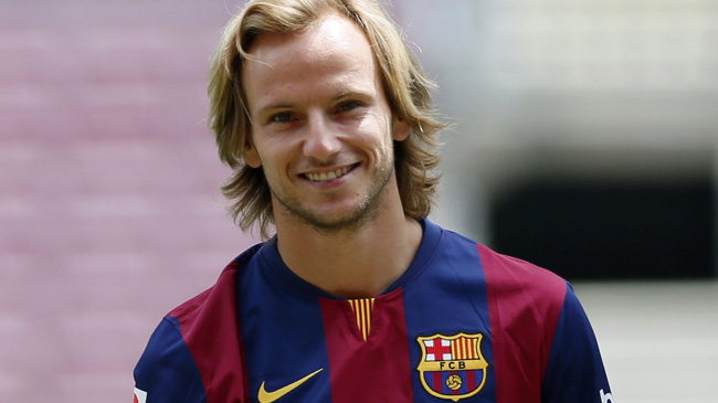 FC Barcelona's newly signed soccer player Ivan Rakitic from Croatia poses for pictures in his new jersey during his presentation at Camp Nou stadium, in Barcelona