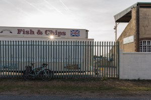 norfolk-f2c bikepacking route at Great Yarmouth racecourse, with a touring bike in front of a fish and chip stand at sunrise.